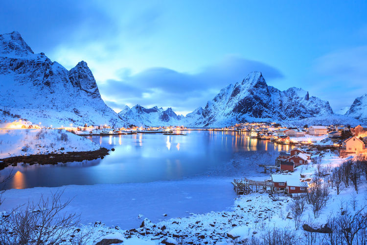 Scenic view of lake and snowcapped mountains against sky at lofoten during dusk