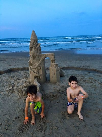 Shirtless friends making castle at beach against sky