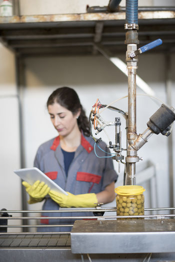 Woman using digital tablet while working in factory