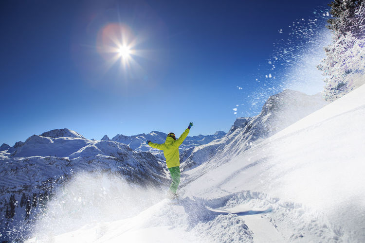 Rear View Of Man With Arms Raised Skiing On Snowcapped Mountains Against Clear Sky
