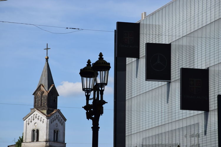 Low angle view of church and lamp posts by building against sky in city