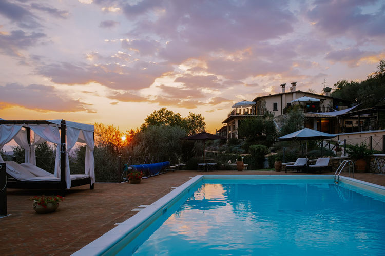 Swimming pool by buildings against sky during sunset