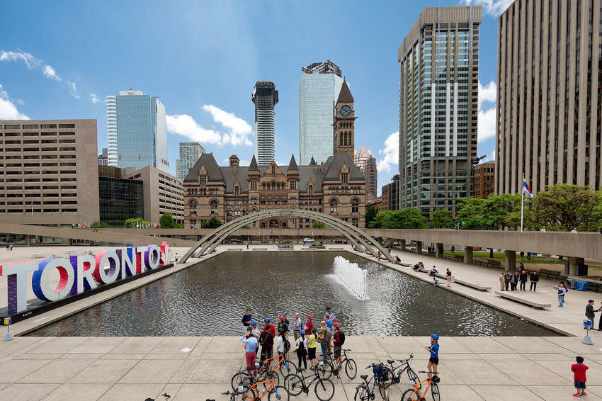 TORONTO, CANADA - JUNE 09, 2018: Beautiful wide view of the Nathan Phillips Square in the city Toronto Canada Architecture Bridge Bridge - Man Made Structure Building Building Exterior Built Structure City Cityscape Crowd Group Of People Large Group Of People Lifestyles Men Modern Nathan Phillips Square Office Building Exterior Outdoors Real People Sky Skyscraper Tall - High Tower Water Women