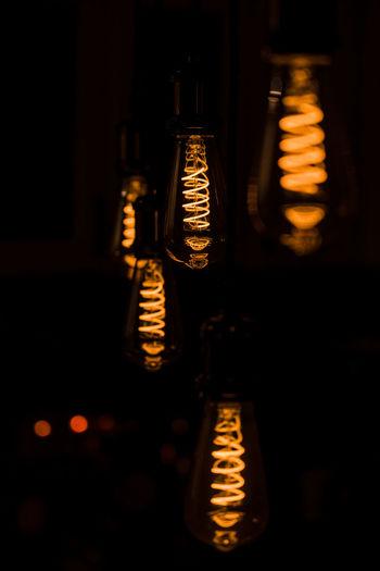 Close-up of illuminated light bulbs in dark room