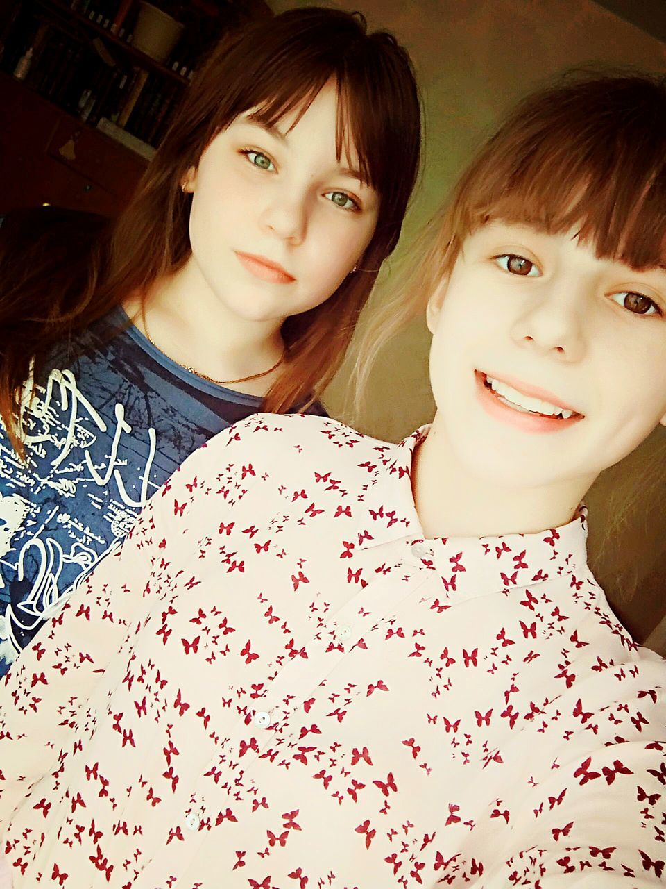 two people, looking at camera, real people, portrait, smiling, togetherness, girls, leisure activity, childhood, indoors, sitting, happiness, lifestyles, young women, young adult, friendship, bonding, day, close-up