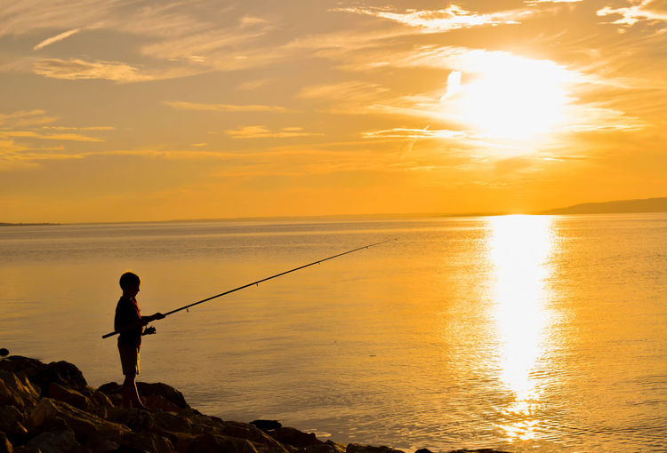 Silhouette Boy Fishing In Sea Against Sunset Sky