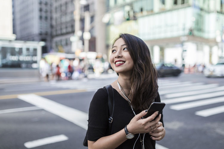 Young woman using phone while standing on road in city