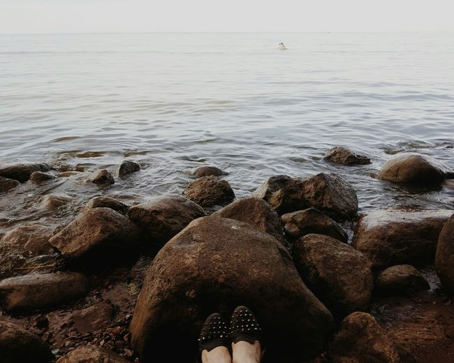 Low section of person on rock in sea