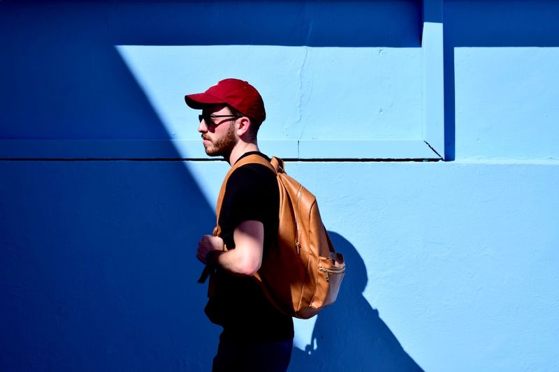 Young Man Walking By Blue Wall