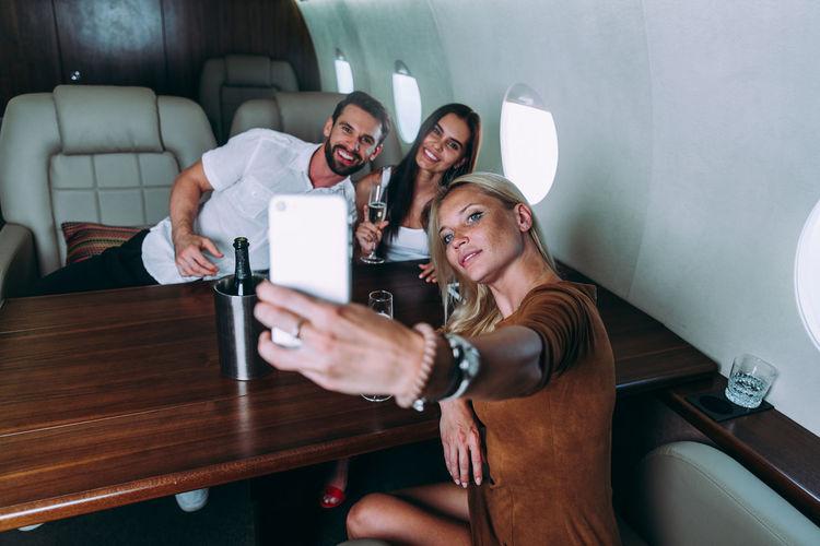 Friends taking selfie on phone in airplane