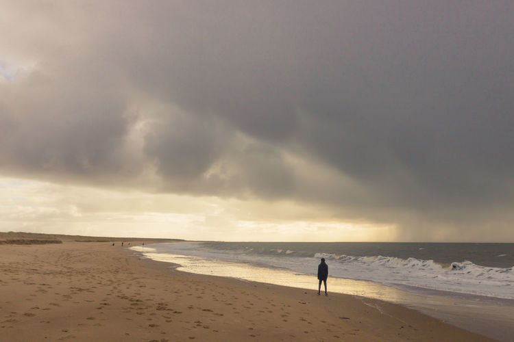 Silhouette man standing at beach against cloudy sky