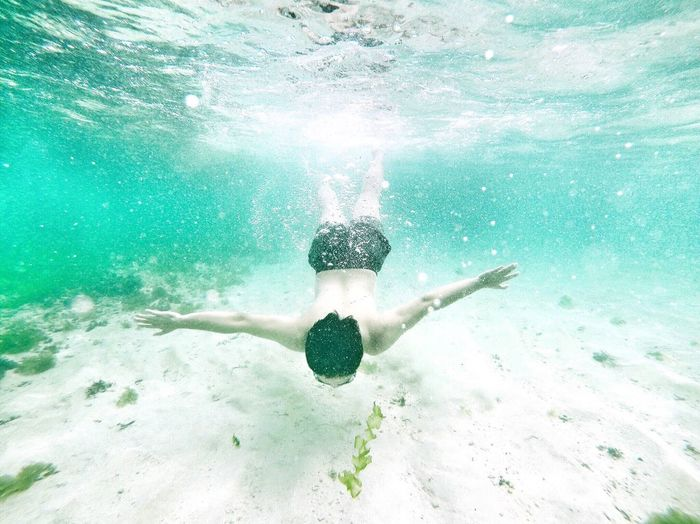 Carefree shirtless man swimming undersea