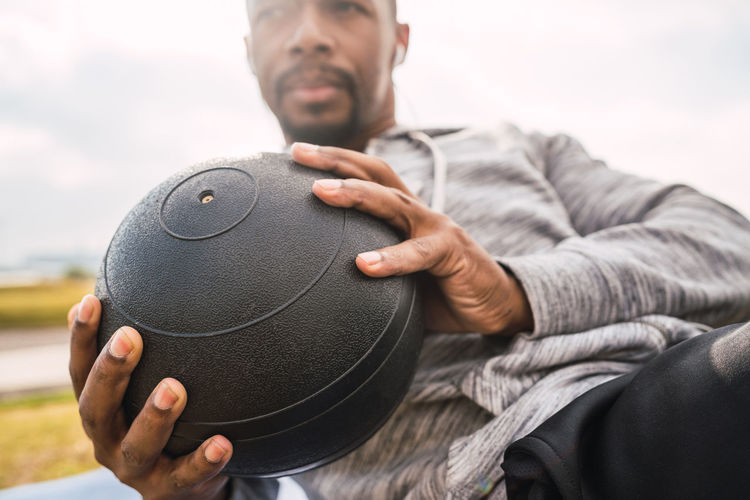 Midsection of man holding ball sitting outdoors
