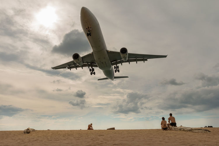 Low Angle View Of Plane Flying Over Beach Against Sky