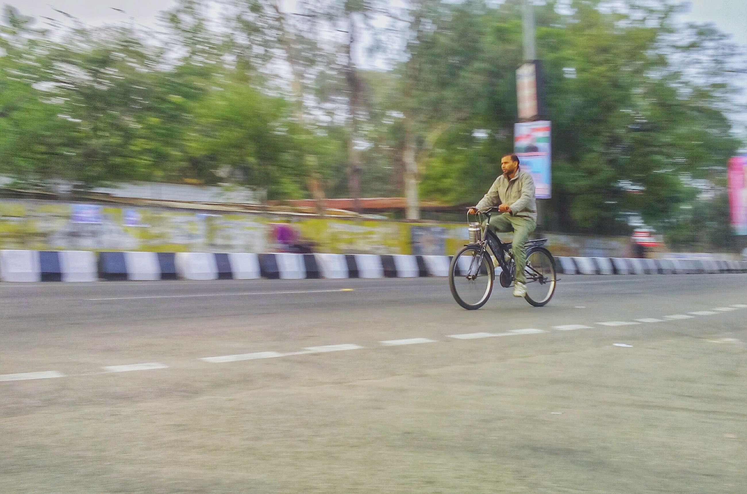transportation, blurred motion, speed, motion, road, real people, riding, bicycle, land vehicle, mode of transport, one person, outdoors, day, tree, full length, nature, people