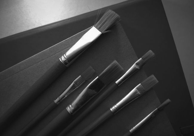 Black and white. Brush range of various sizes Still Life Table Indoors  High Angle View No People Close-up Wood - Material Art And Craft Pen Metal Creativity Group Of Objects Writing Instrument Choice Furniture Variation Craft Medium Group Of Objects Equipment Knife