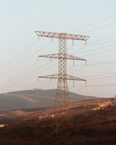 Low angle view of electricity pylon on field