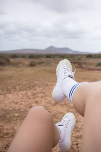 Low section of woman wearing shoes on land