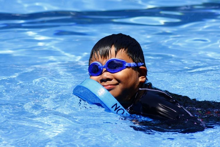 Side view of boy with kickboard in swimming pool
