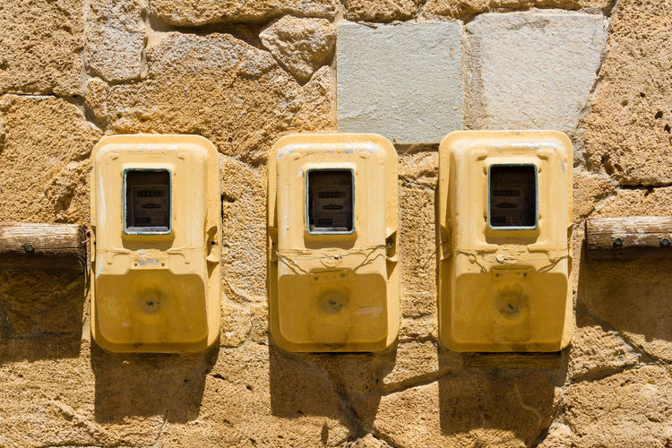 Close-up of three Electrical Boxes on an old Stone Wall Beige Desert Electric Hanging Power Sunlight Wall Architecture Boxes Cables Close-up Day Electricity  Electricity Meter Energy Heat No People Old Outdoor Outdoors Sand Stone Yellow