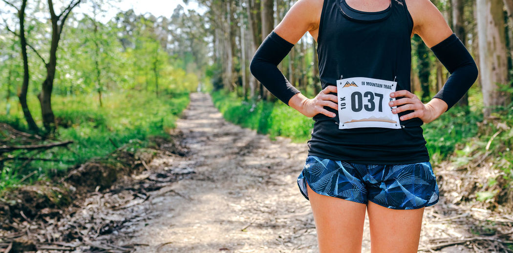 Midsection of woman standing with marathon bib in forest