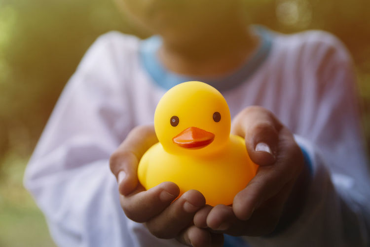 Boy holding yellow rubber duck Childhood Close-up Day Finance Focus On Foreground Freshness Front View Holding Human Body Part Human Hand Lifestyles Midsection One Person People Real People Rubber Duck Yellow