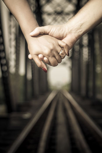 Close-up of woman hand on railroad tracks