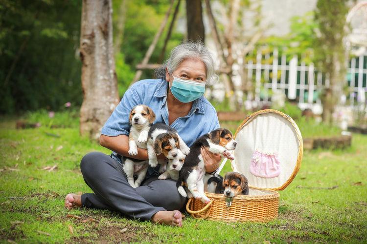 Senior woman wearing mask holding puppies sitting outdoors