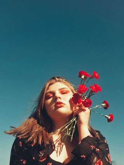 Portrait of young woman with red flowers against blue sky