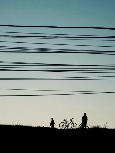 Silhouette people riding bicycle on field against sky