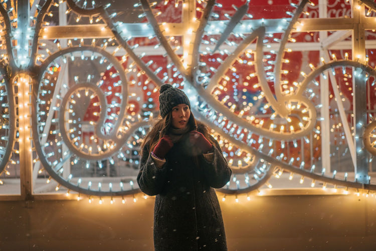 Christmas Christmas Decoration Portrait New Year One Person Standing Illuminated Young Adult Front View Smiling Arts Culture And Entertainment Looking At Camera Young Women Adult Night Winter Leisure Activity Beauty Women Emotion Three Quarter Length Warm Clothing Beautiful Woman Outdoors Hairstyle Snowing