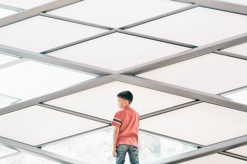 Low angle view of boy standing on ceiling