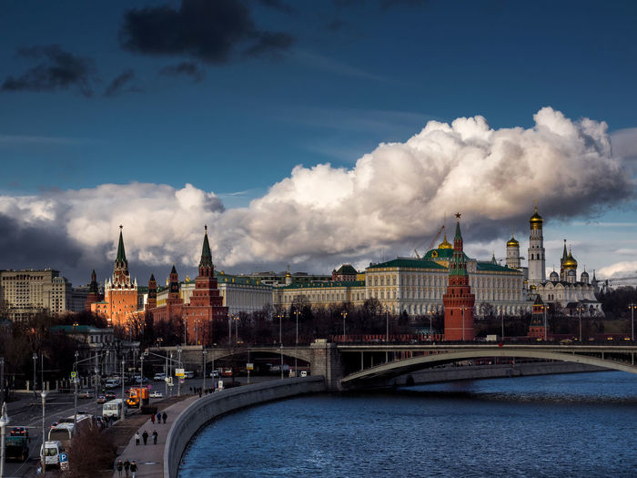 Moscow kremlin by river in city against sky