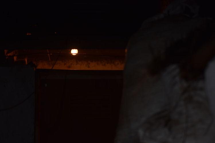 Rear view of silhouette person in illuminated dark room