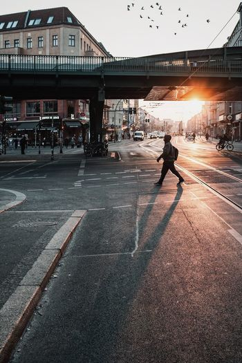 People walking on road in city against sky at sunset