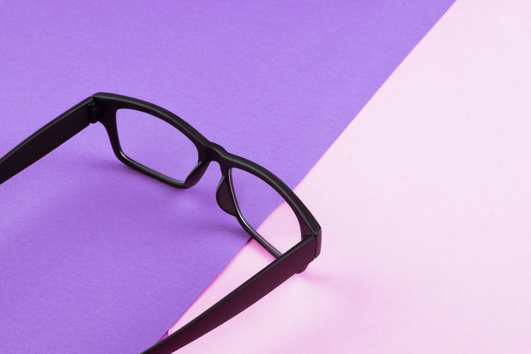 eye glasses spectacles with shiny black frame on pastel color background Pink Color Eyeglasses  Glasses Indoors  No People Copy Space Still Life Eyesight Single Object Close-up High Angle View Studio Shot Purple Blue Table Colored Background Transparent Glass - Material Cut Out Black Color Personal Accessory