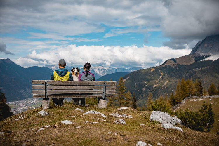 Couple With Dog Sitting On Bench By Mountains Against Cloudy Sky