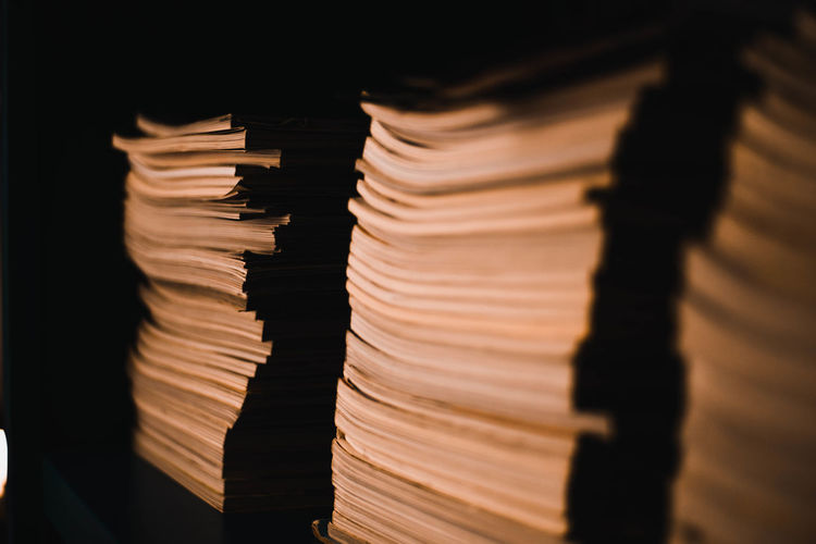 Close-up of stacked books against black background