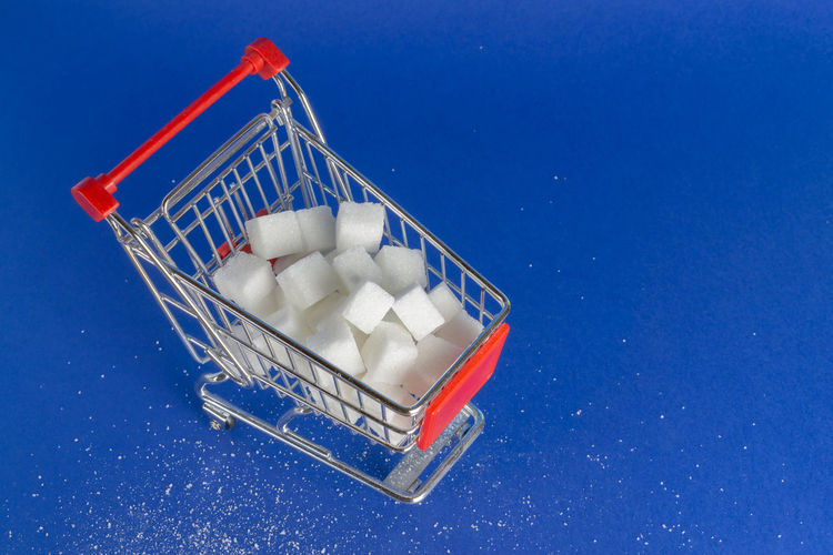 A shopping cart with sugar cubes, blue background and copy space Cubes Sugar Shopping White Cart Background Concept Filled Food Object Lifestyle Sweet Group Energy Eating Ingredient Sale Crystal Push Unhealthy Design Symbol Bright Creative Diet Nutrition Conceptual Buy Basket Cube Consumerism Nobody Container Carbohydrates Blue Still Life Food And Drink High Angle View Colored Background Sweet Food
