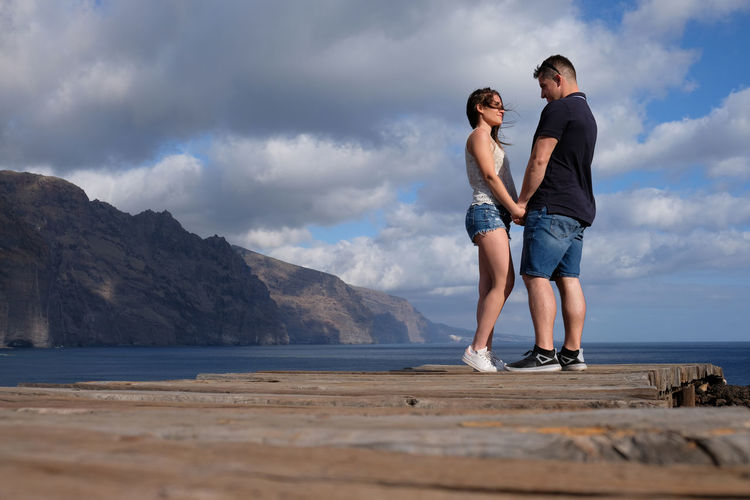 Full length of couple standing on pier over sea against cloudy sky