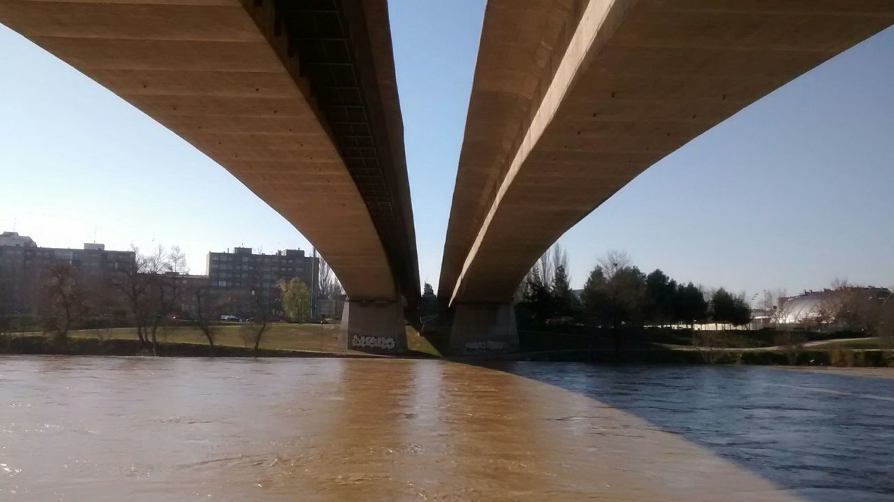 bridge - man made structure, connection, architecture, built structure, river, engineering, transportation, below, underneath, bridge, water, outdoors, city, covered bridge, day, no people, under, road, clear sky, sky, tree