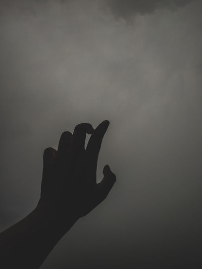 Close-up of silhouette hand holding sun against sky