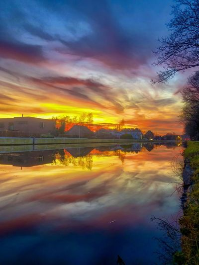 Dramatic and colorful sunset over the river with the gold, yellow, orange, red, purple and blue colors of the sky and the Clouds reflected in the water Cloud - Sky Sky Sunset Reflection Water Scenics - Nature Nature Beauty In Nature Tranquility Tranquil Scene No People Orange Color Plant Lake Tree Dramatic Sky Outdoors Transportation Dusk