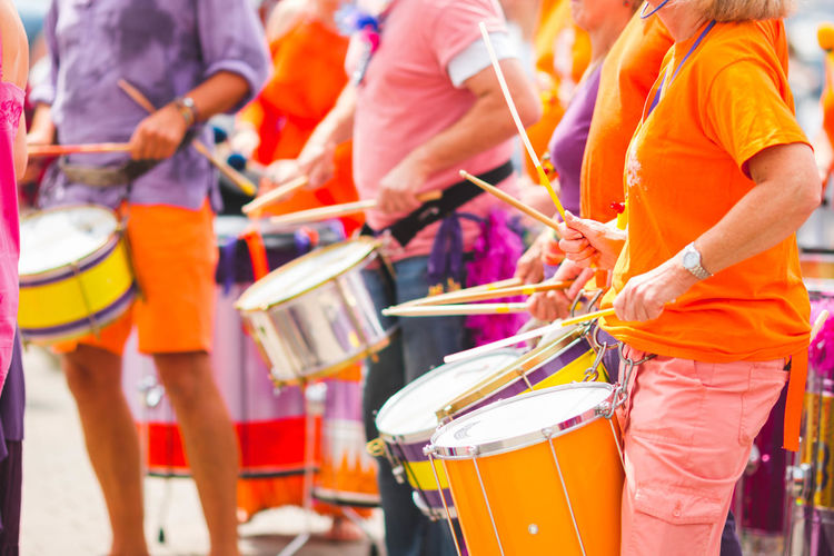 Colors of music Arts Culture And Entertainment City Crowd Day Festival Focus On Foreground Group Group Of People Incidental People Lifestyles Men Midsection Music Musical Equipment Musical Instrument Orange Color Outdoors Real People Standing Street Women
