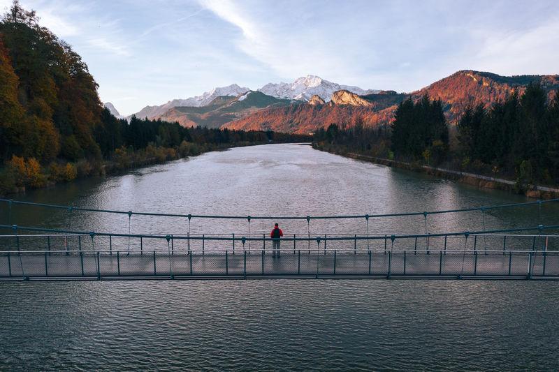 Aerial view of man standing on bridge over salzach river at sunset, salzburg, austria.
