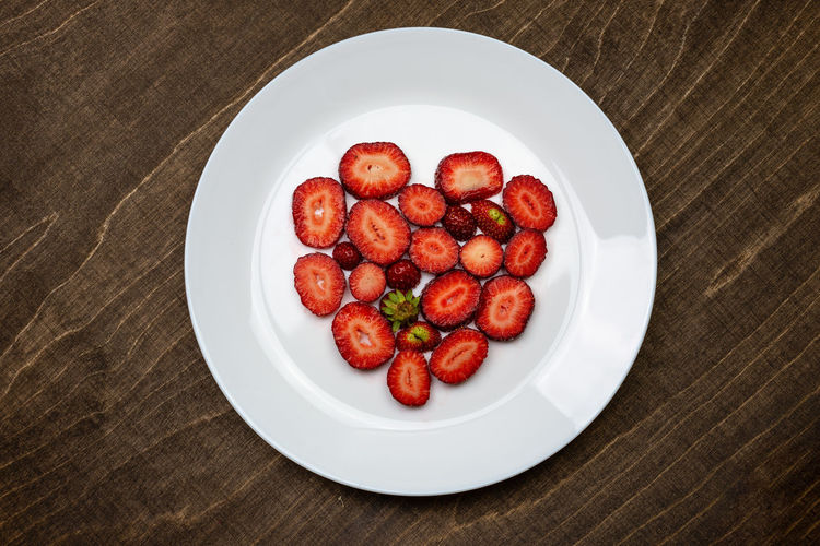 Creative Valentine Day romantic concept composition flat lay top view with heart strawberries on a white plate on a wooden table. Food And Drink Food Freshness Red Indoors  Still Life No People Strawberry Strawberries Fruit Fruits Fresh Healthy Eating Natural Raw Vitamin Raw Food Tasty Breakfast Ripe Sweet Berry Delicious Nutrition Background Rustic Dessert Freshness Eating Organic Close-up Diet Ingredient Vegan Snack Apperitive Pattern Wooden Table Brown Texture Bowl Plate Ceramic Flat Lay High Angle View Wood - Material Vegetable Crockery Heart Directly Above