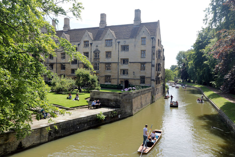 People on river amidst trees and buildings