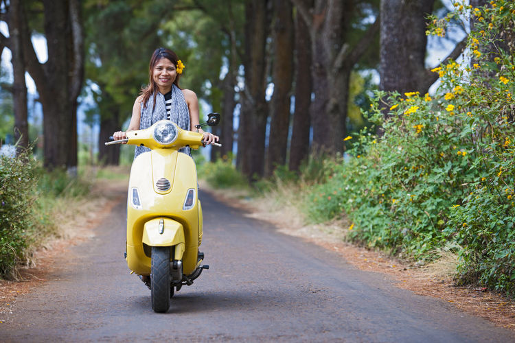 Portrait of woman riding motorcycle on road