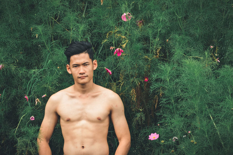 Portrait of shirtless young man standing in garden
