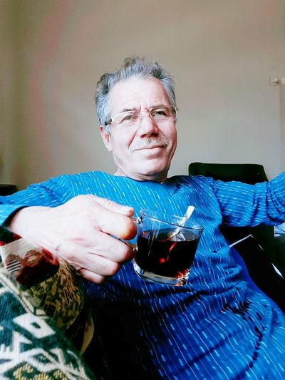 Portrait of senior man having drink while sitting at home
